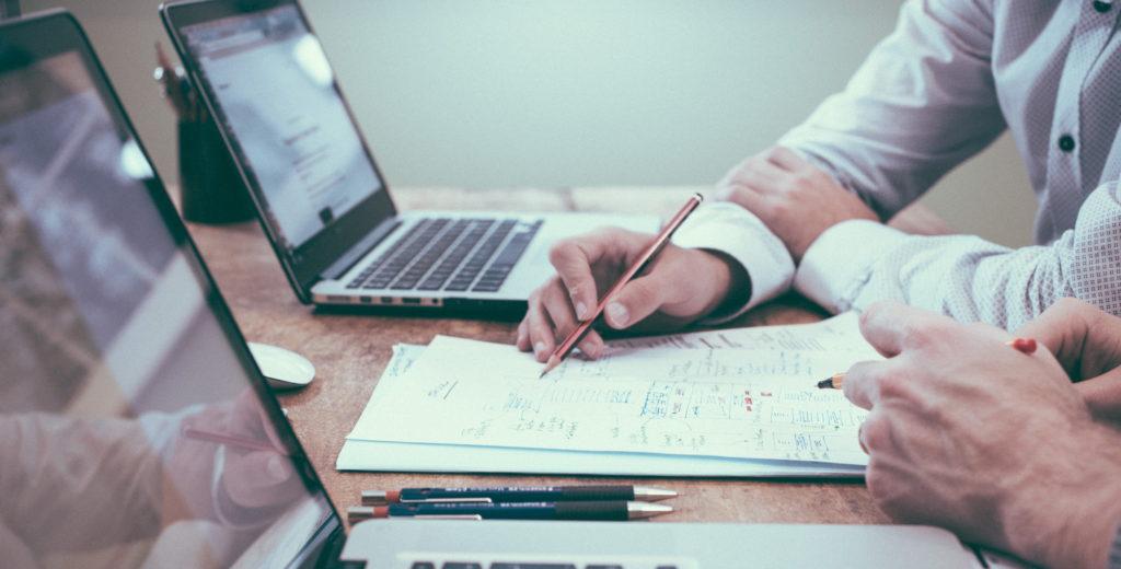 Ein Schreibtisch mit Laptop und Notizen, an dem zwei Personen eine Besprechung abhalten.